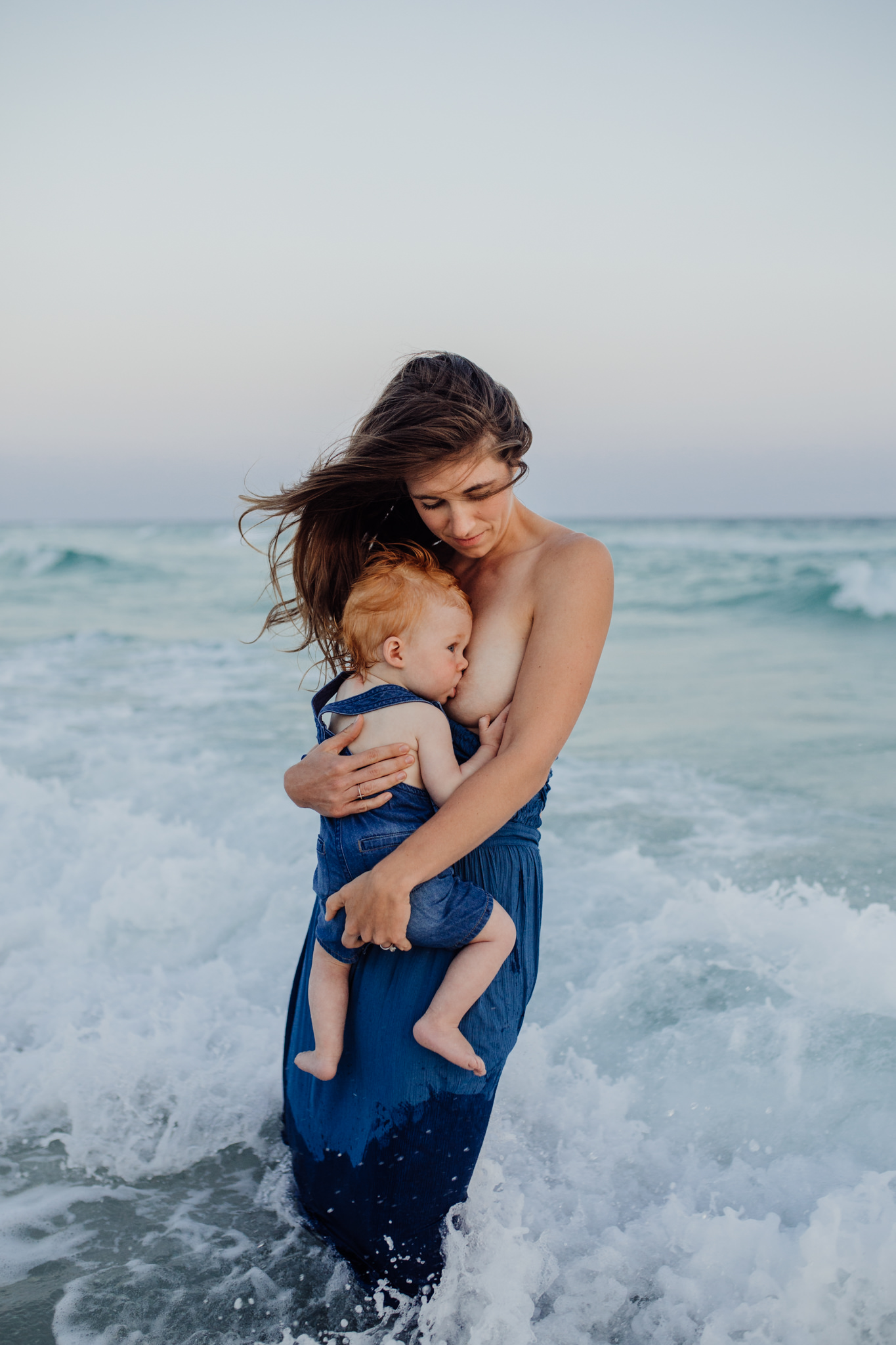 A woman breastfeeding her newborn while standing in the ocean