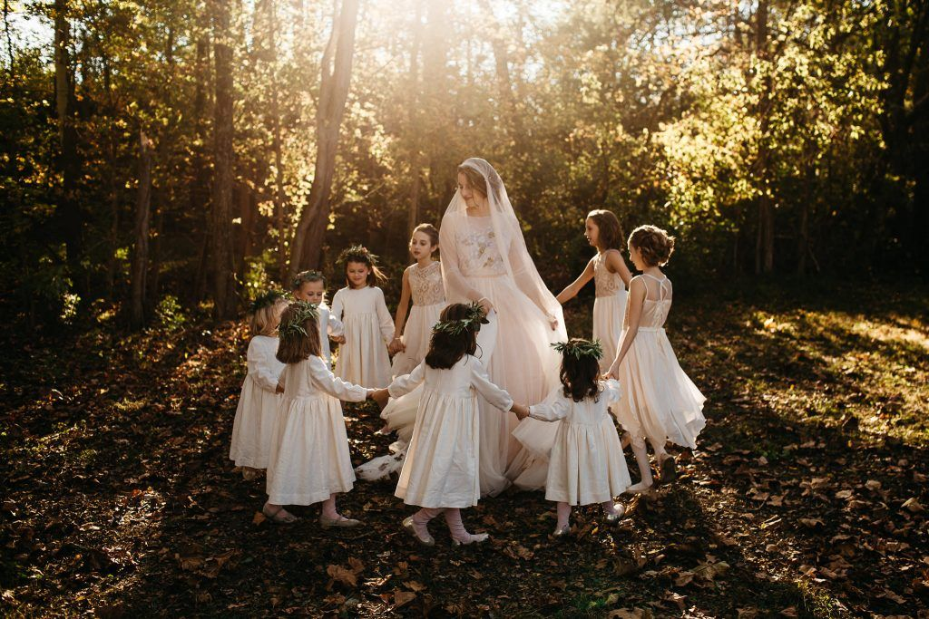 A bride and children are dancing in the forest.