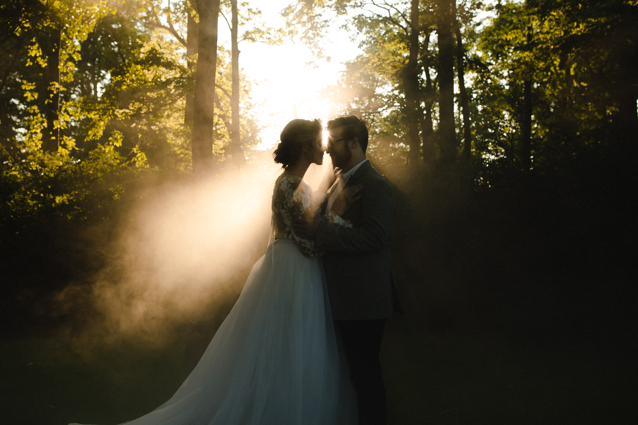 A wedding couple is standing in the forest, captured by a wedding photographer Ohio.