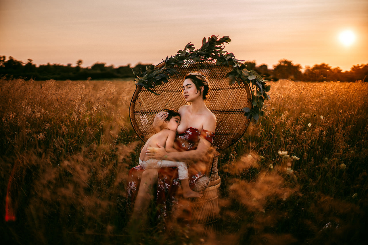 A mother breastfeeding her baby while sitting in a chair at sunset