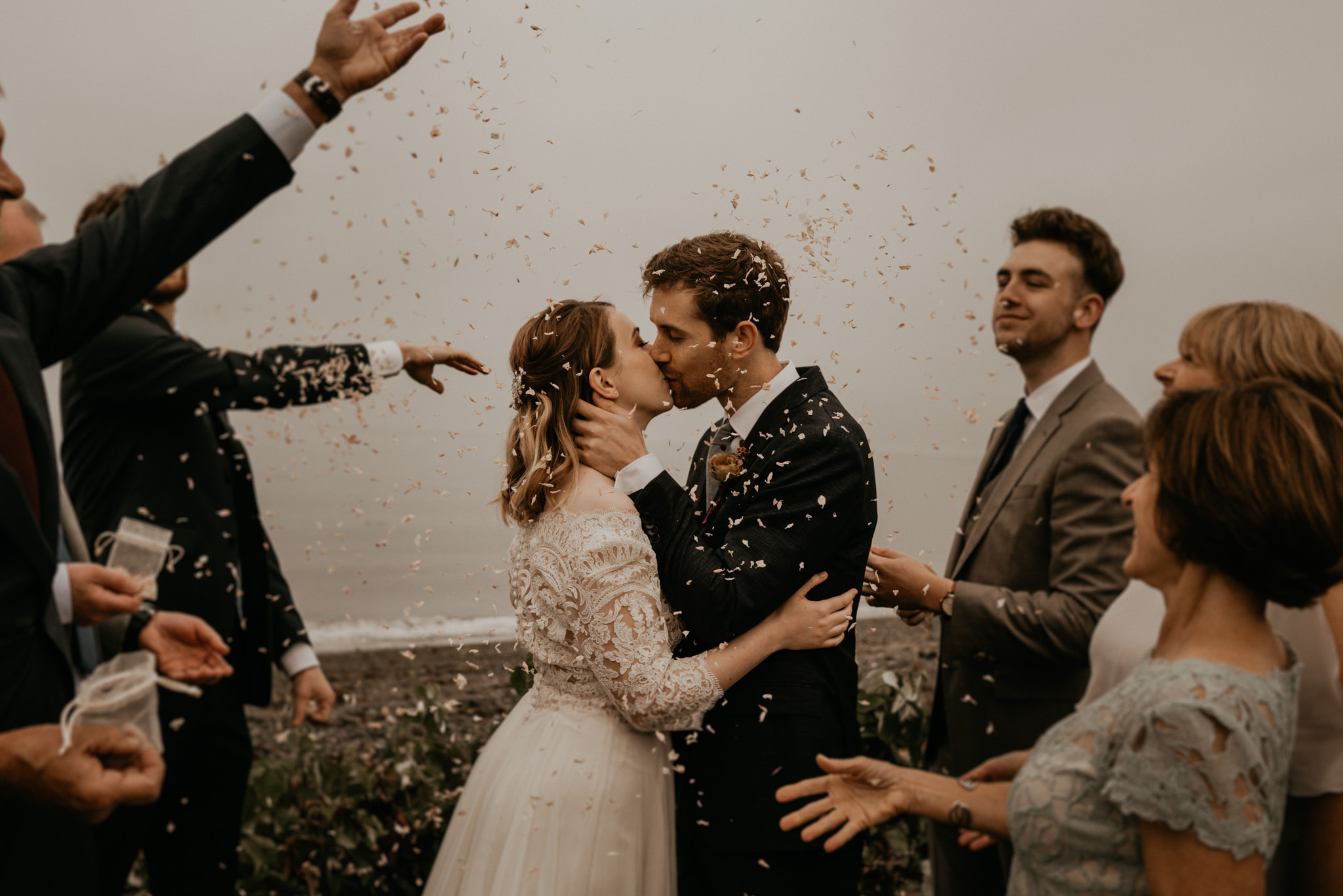 A wedding couple is kissing each other and their guests are cheering, photographed by a wedding photographer Seattle.