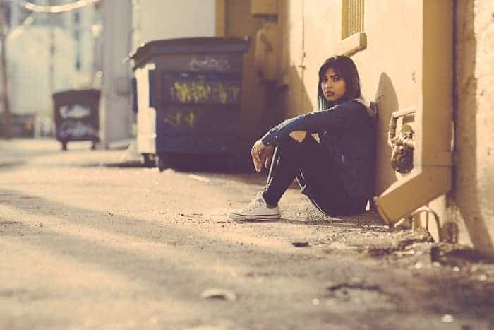young girl sitting in a back alley
