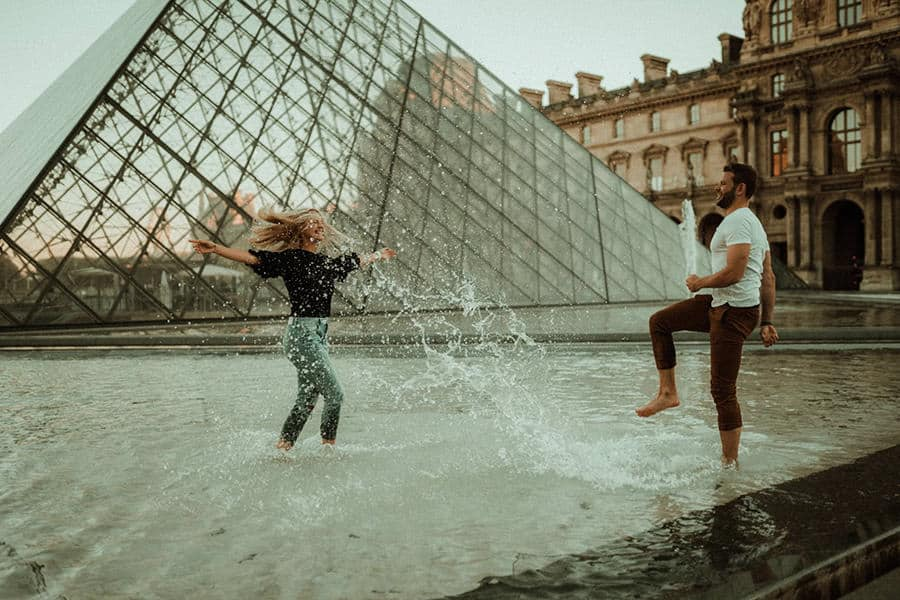 A man playing with a girl in front of a Louvre fountain