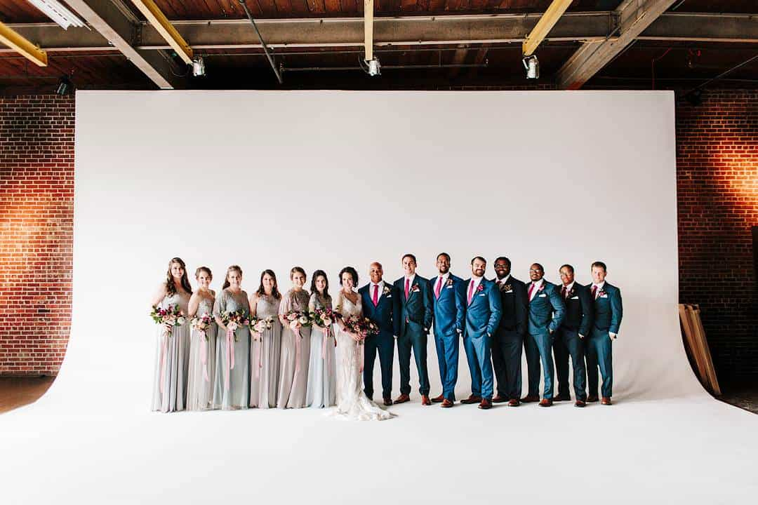 Best men and bridesmaids are surrounding the newlyweds in front of a white background in a studio.