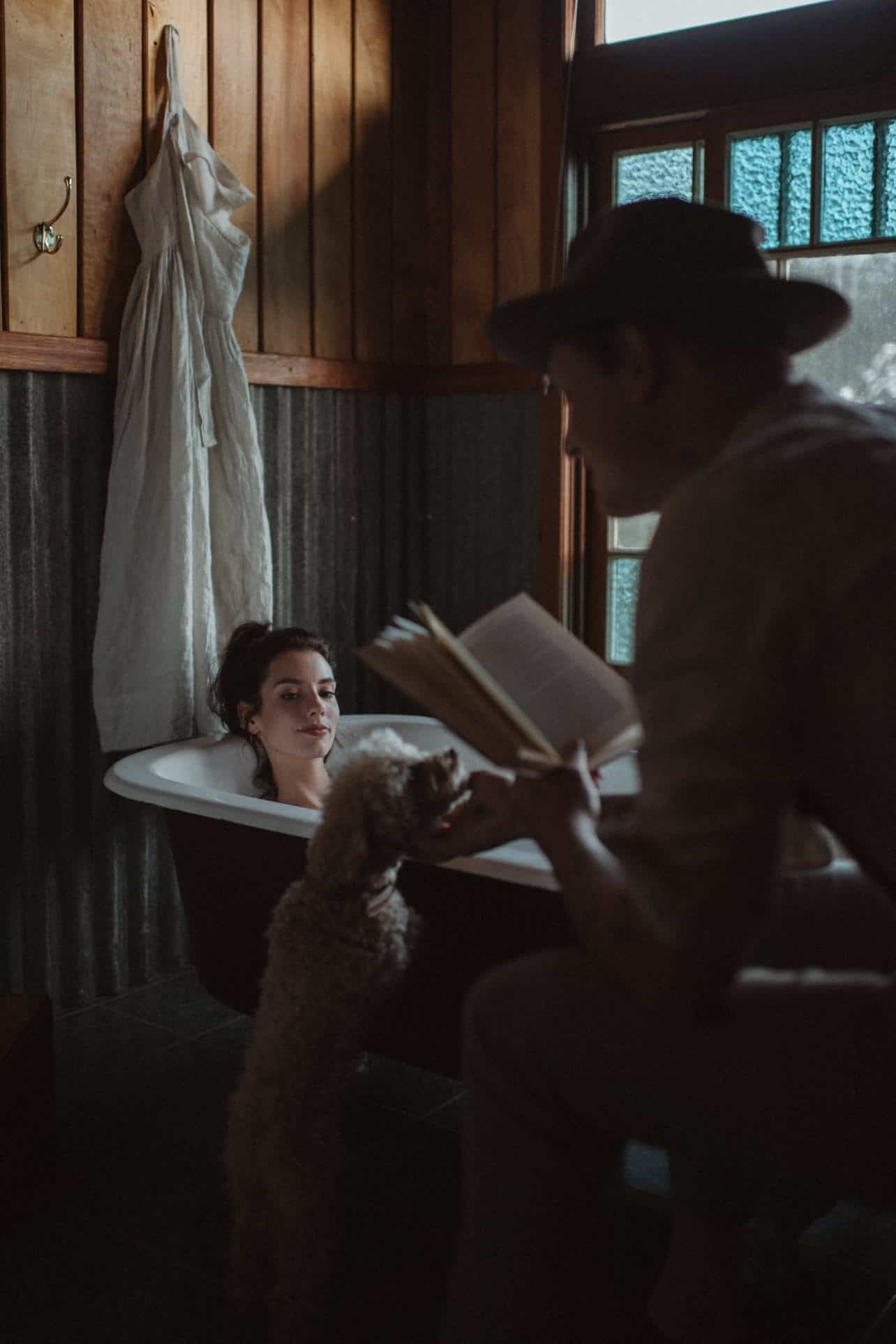 A man reads a book to his wife while she is sitting in the bathtub