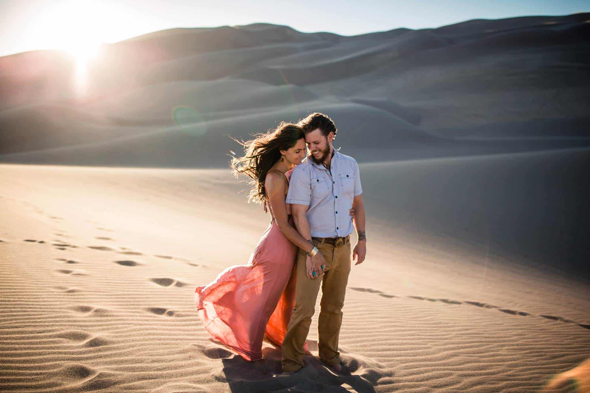 A woman embracing her man in the desert at sunset