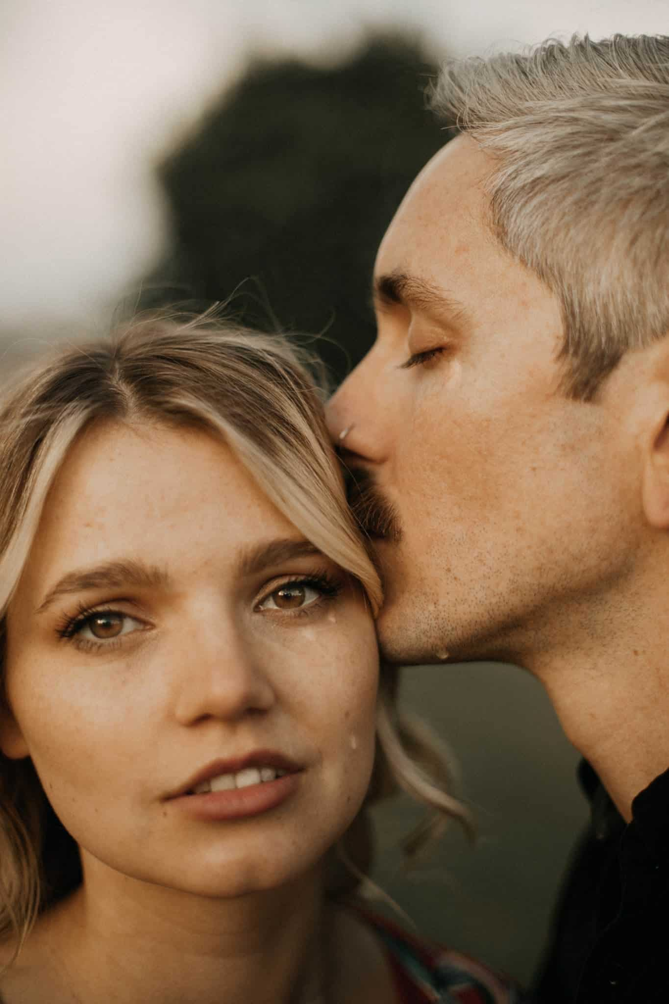 Close up of a man kissing his woman on her forehead