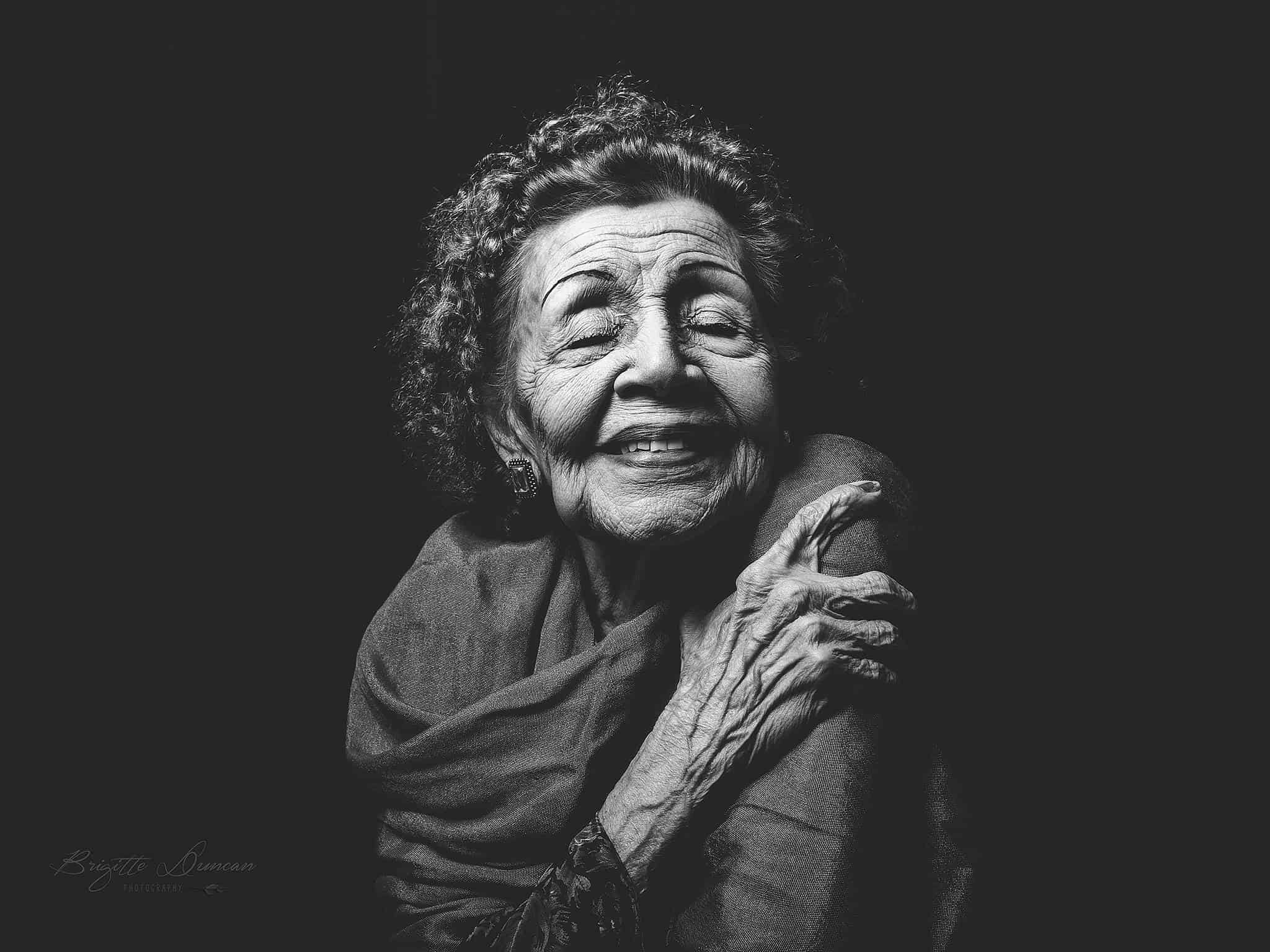 An old woman has closed her eyes, holds her left arm and smiles