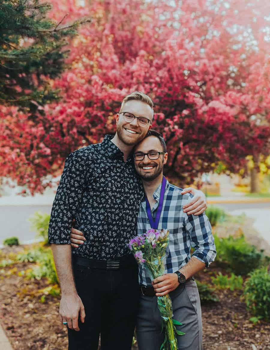 A happy gay couple in front of a red tree