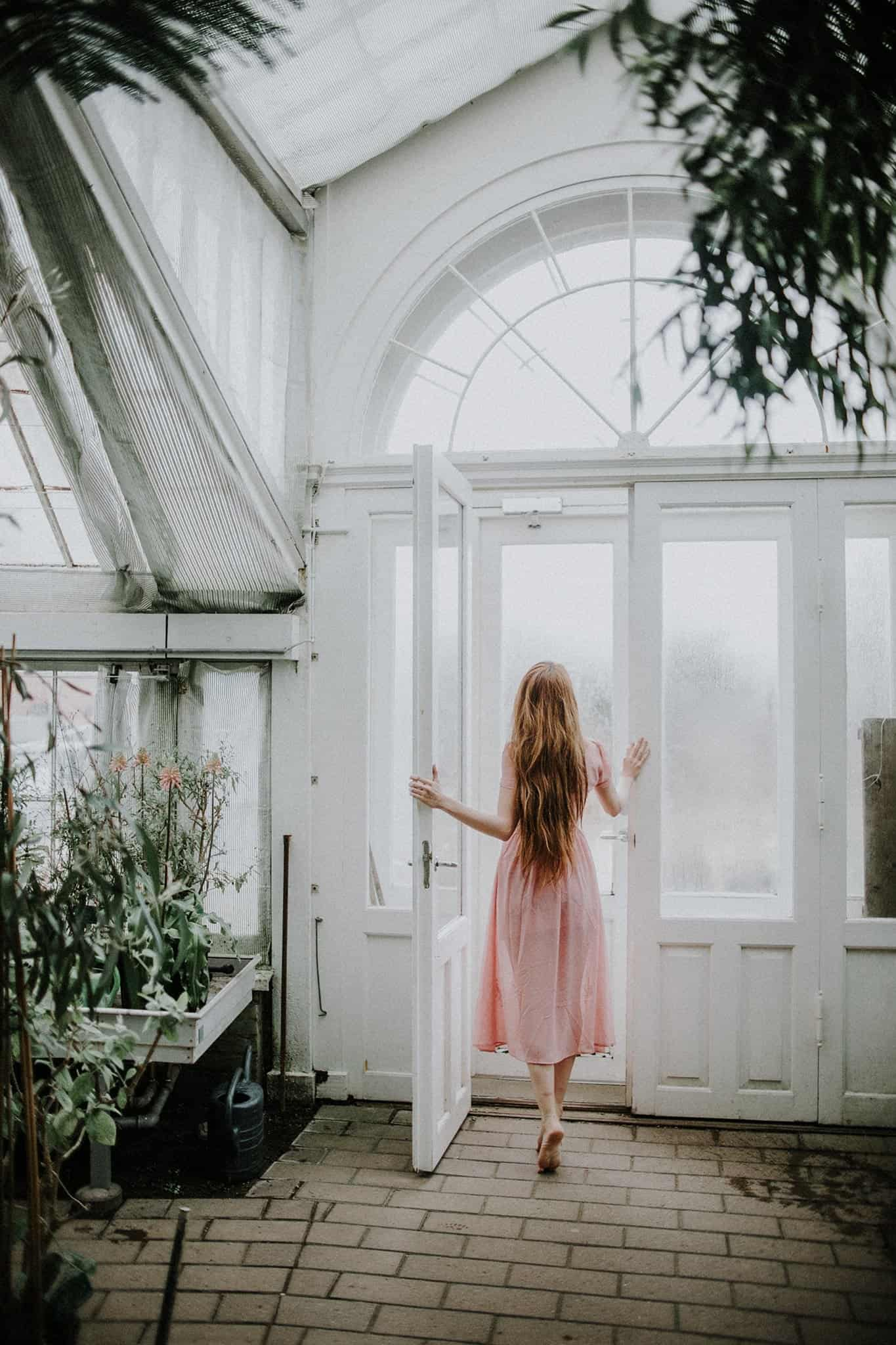 A girl is walking out through a door in a greenhouse