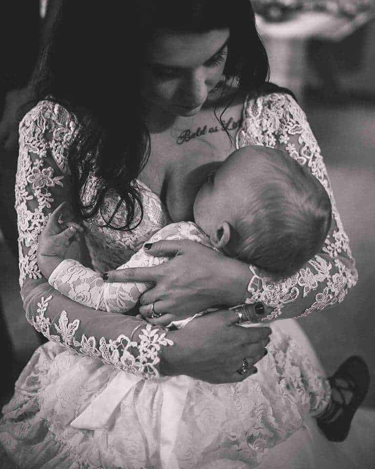 Breastfeeding photo of a bride nursing her baby at a wedding
