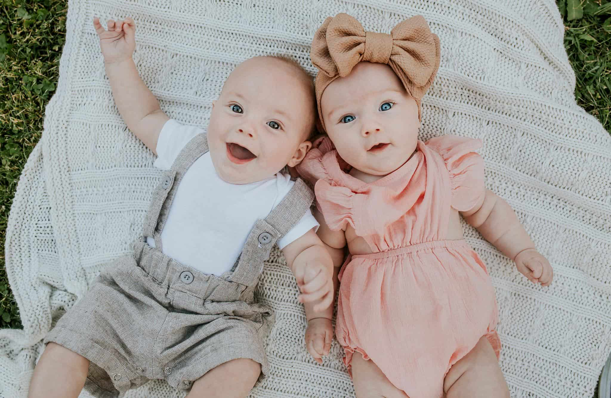 Two newborns dressed up nicely laying on a blanket