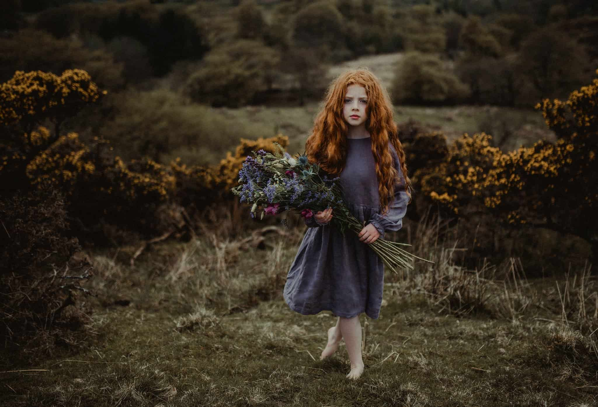 A girl that looks like Merida standing in a field holding flowers