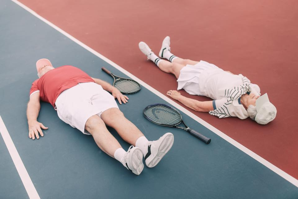 An old couple is laying on the floor with tennis rackets between them