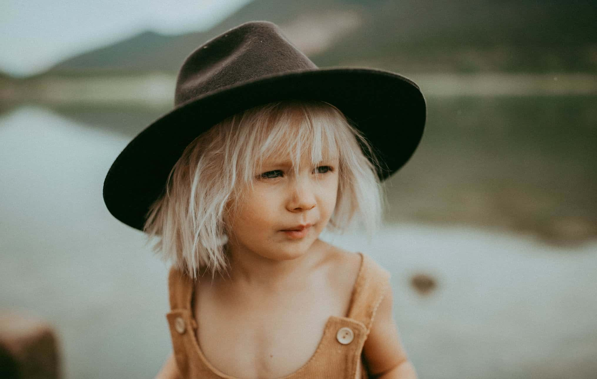 Small kid with a hat that looks into the distance