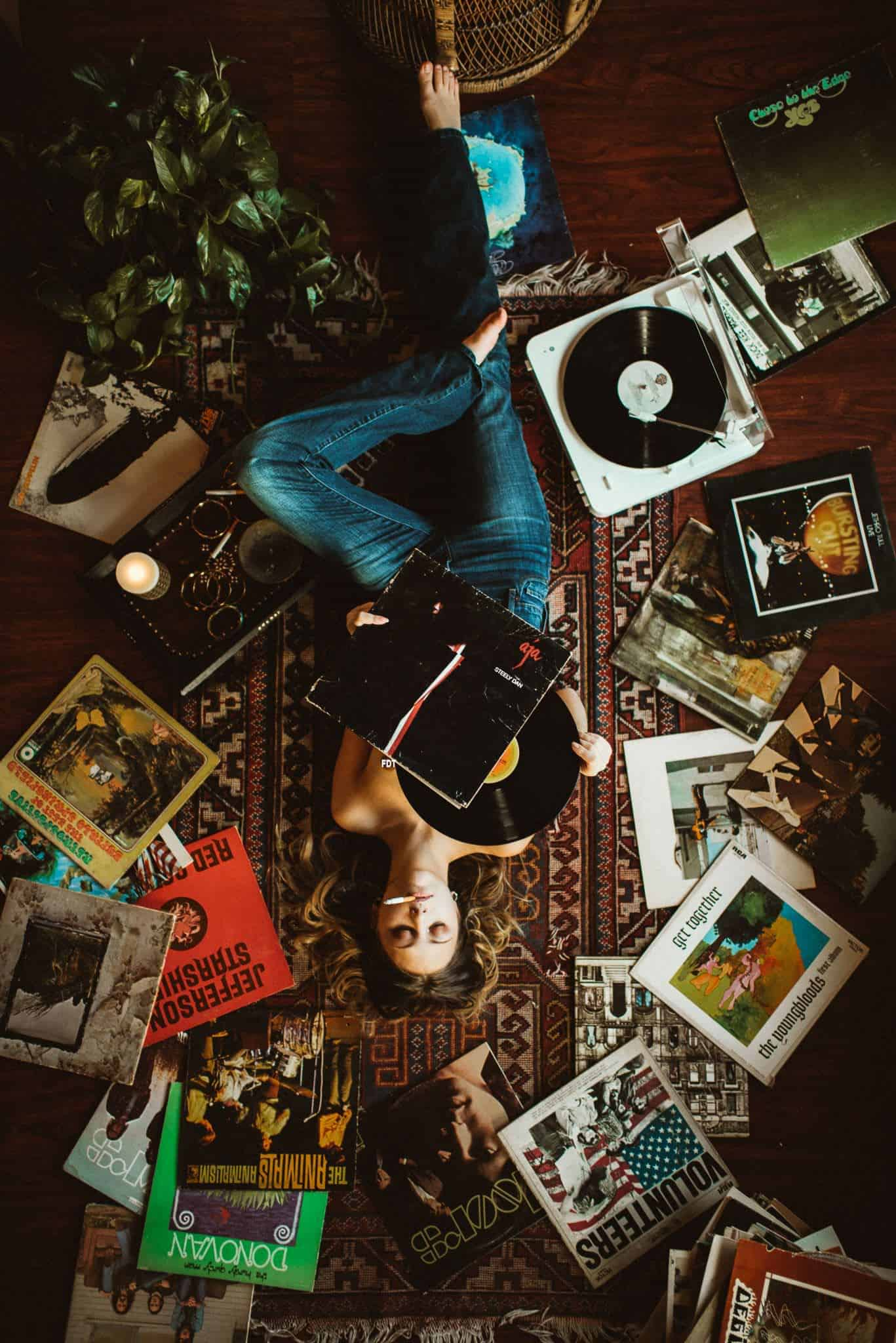 A young woman is lying on a carpet and looks through some pieces of vinyl while smoking.