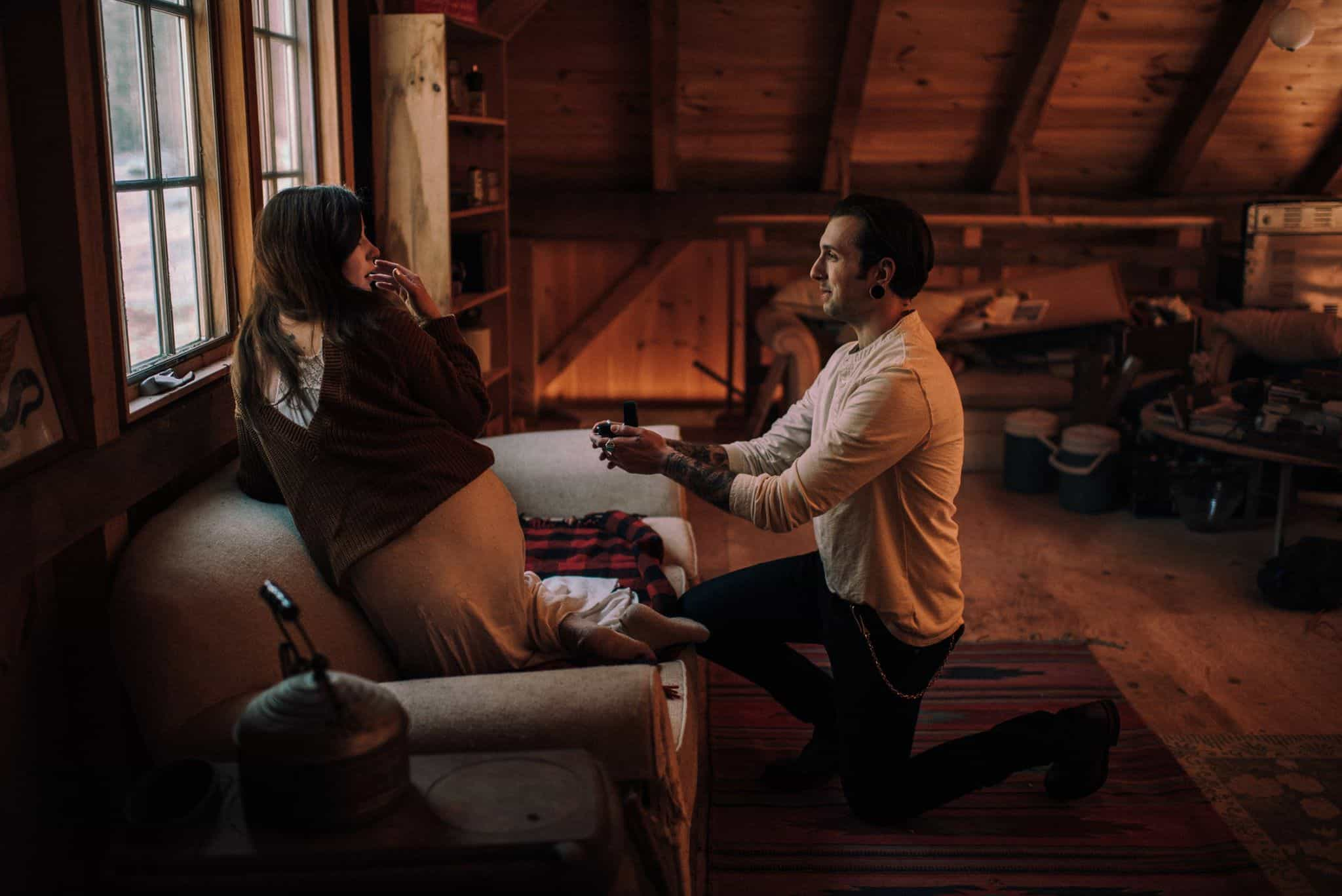 A man proposing to a surprised woman in a cabin