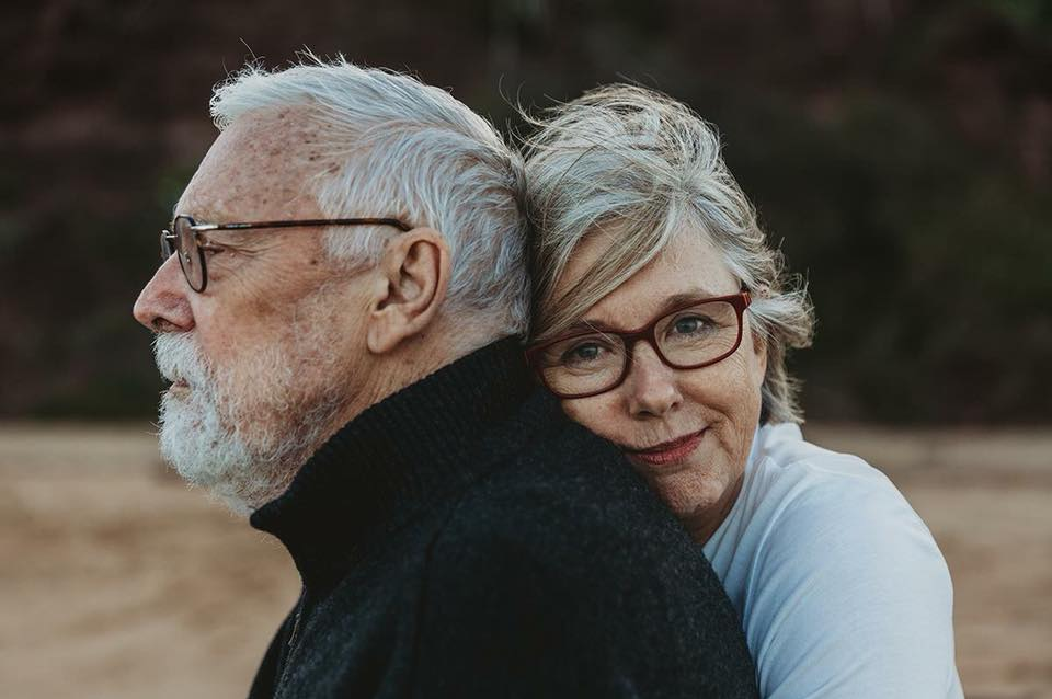 Two elderly people hugging while wearing glasses