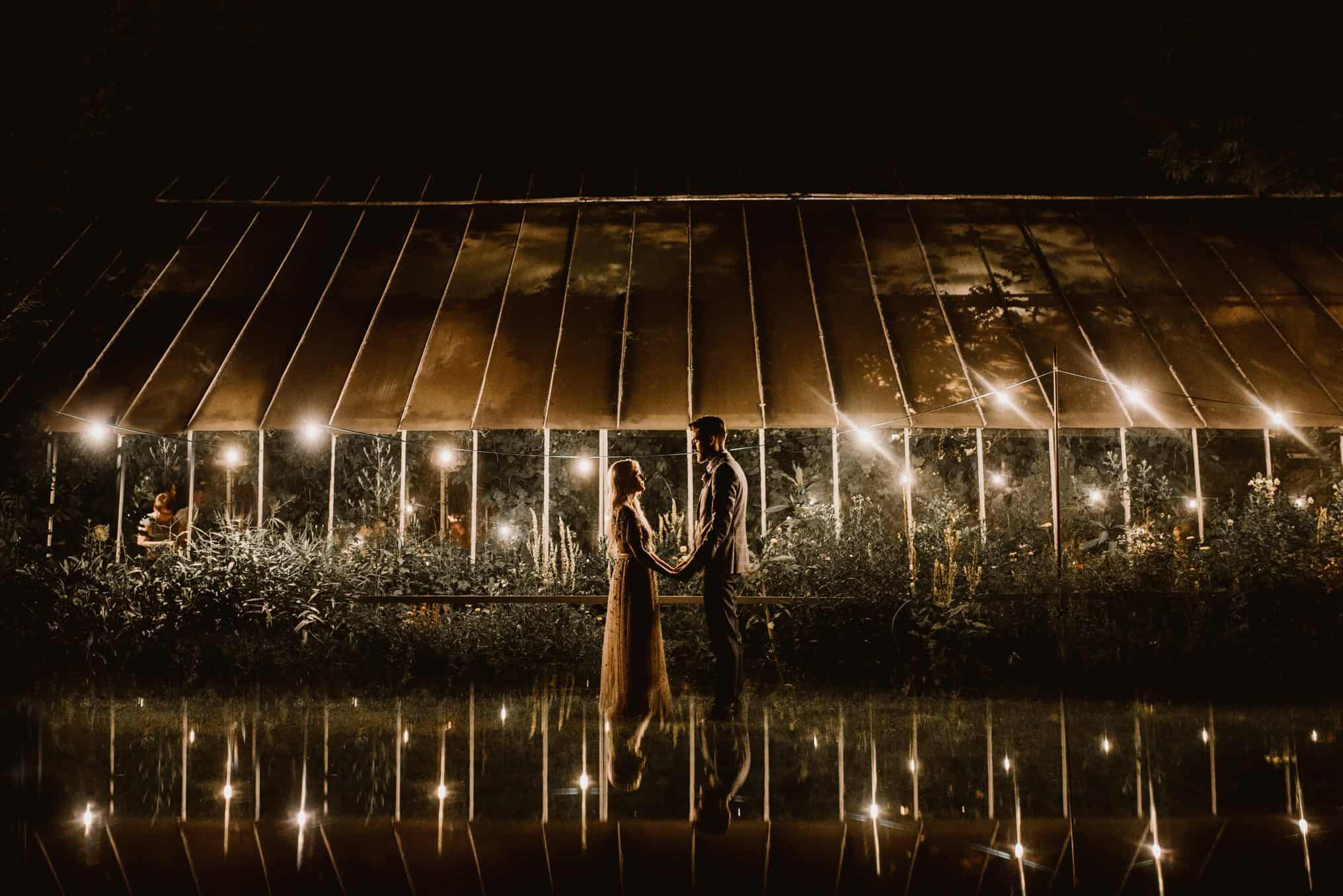 A nighttime couple shot in front of a lit up wedding venue