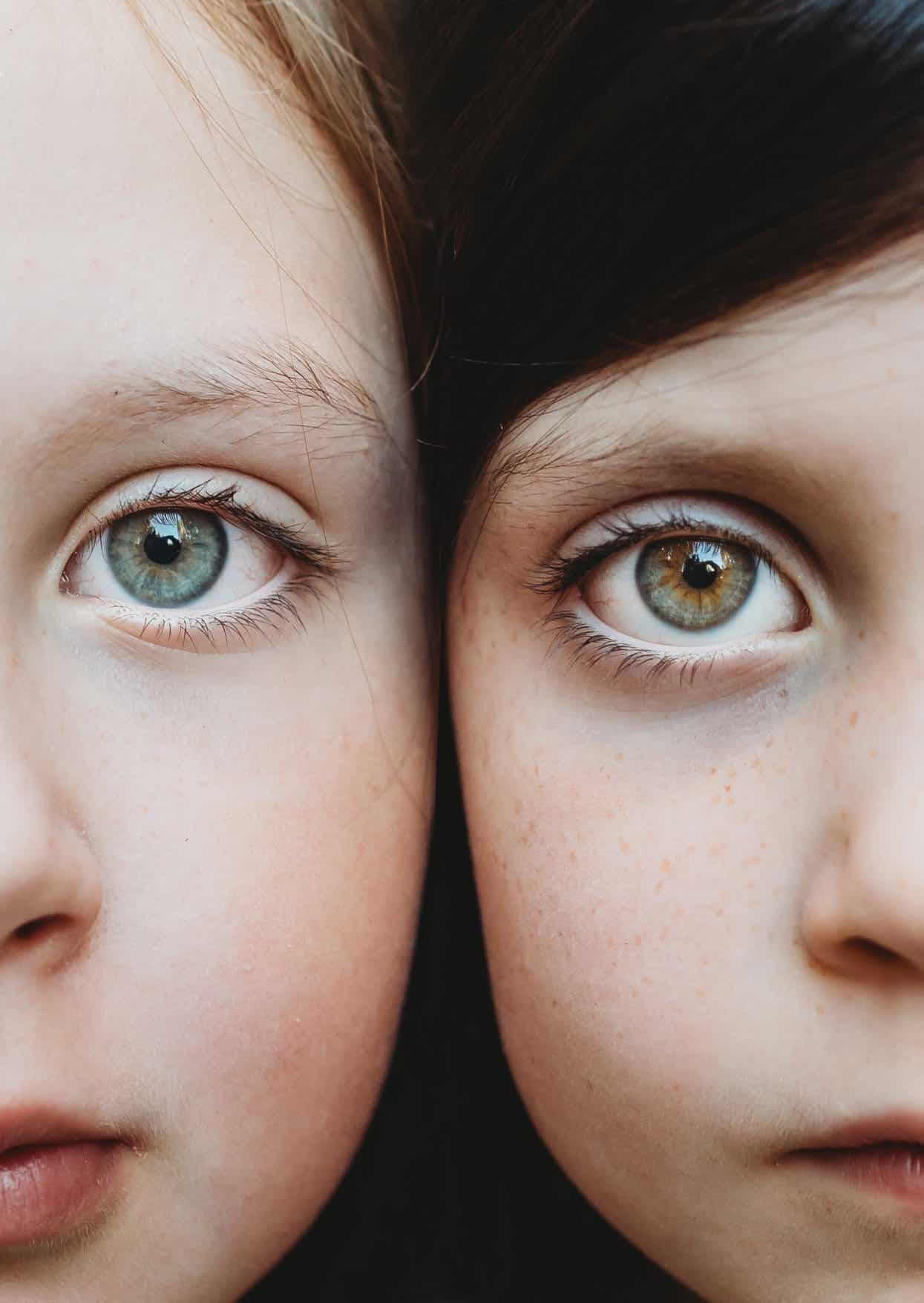 A close up of two sisters close to each other with their faces