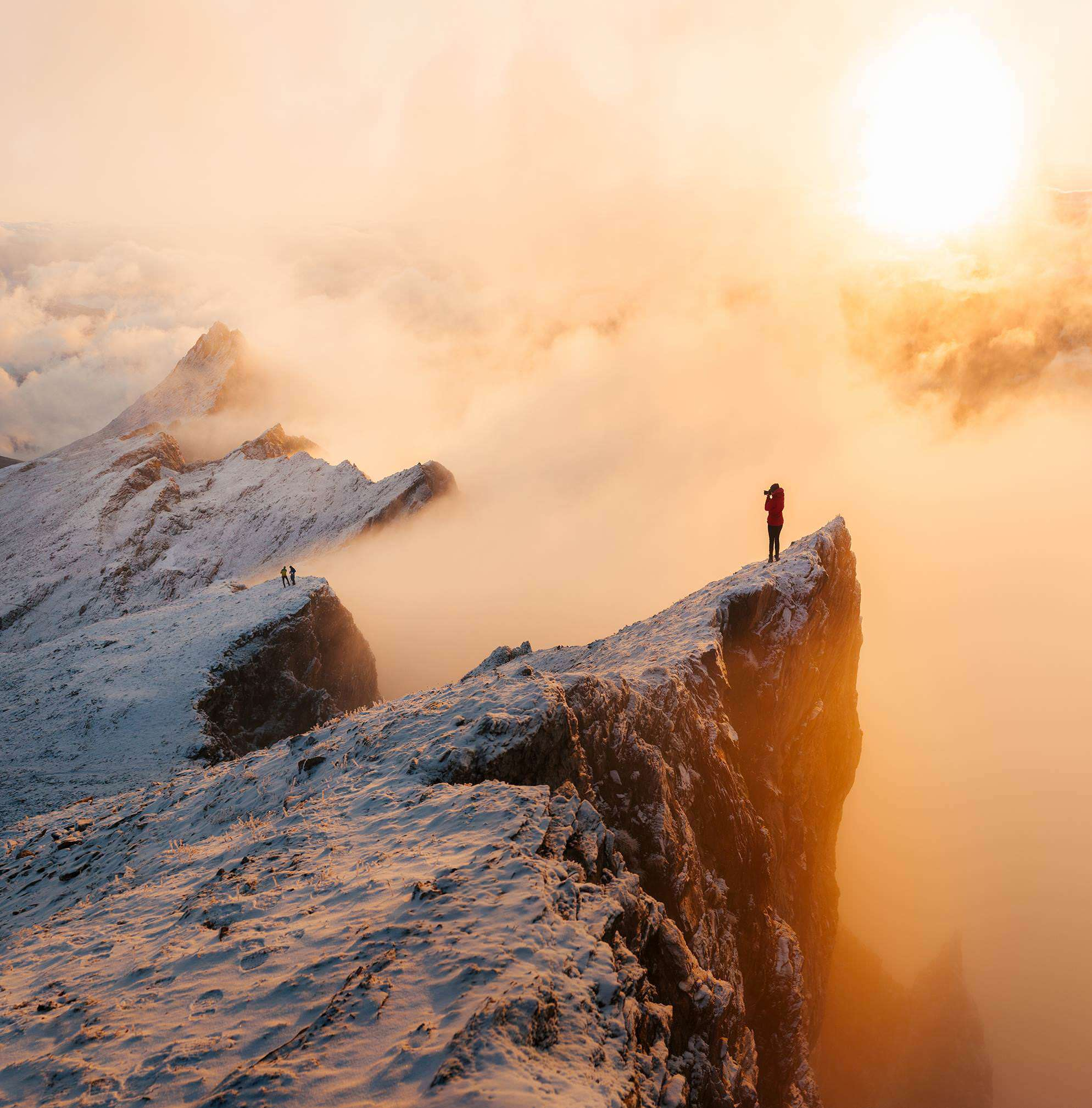 A woman standing on the edge of a snowy mountain is photographing a couple while the clouds cover the sun.