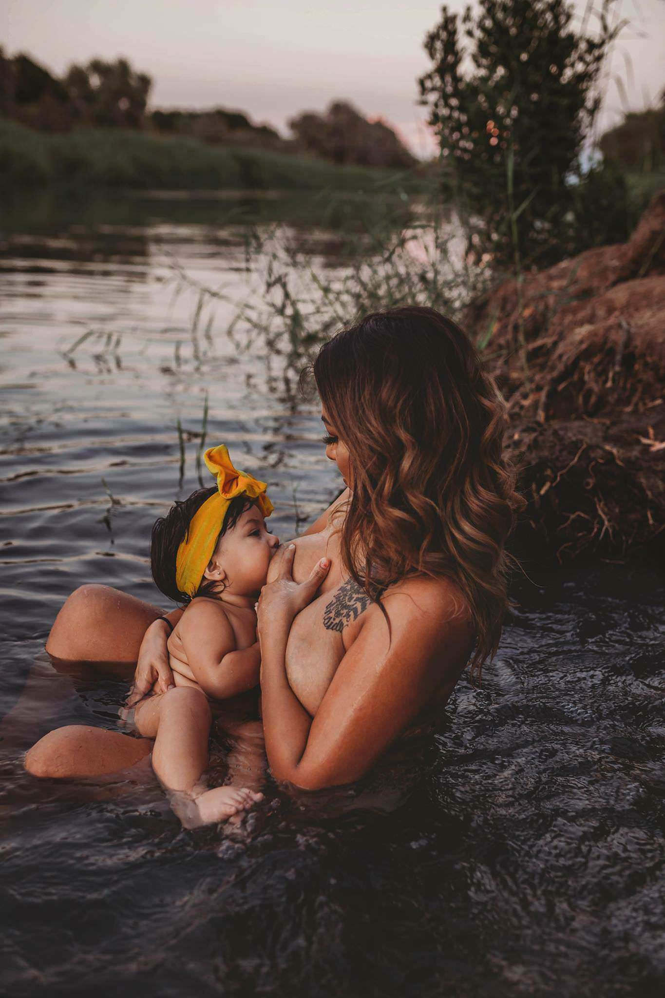 A mother nursing her daughter In a lake