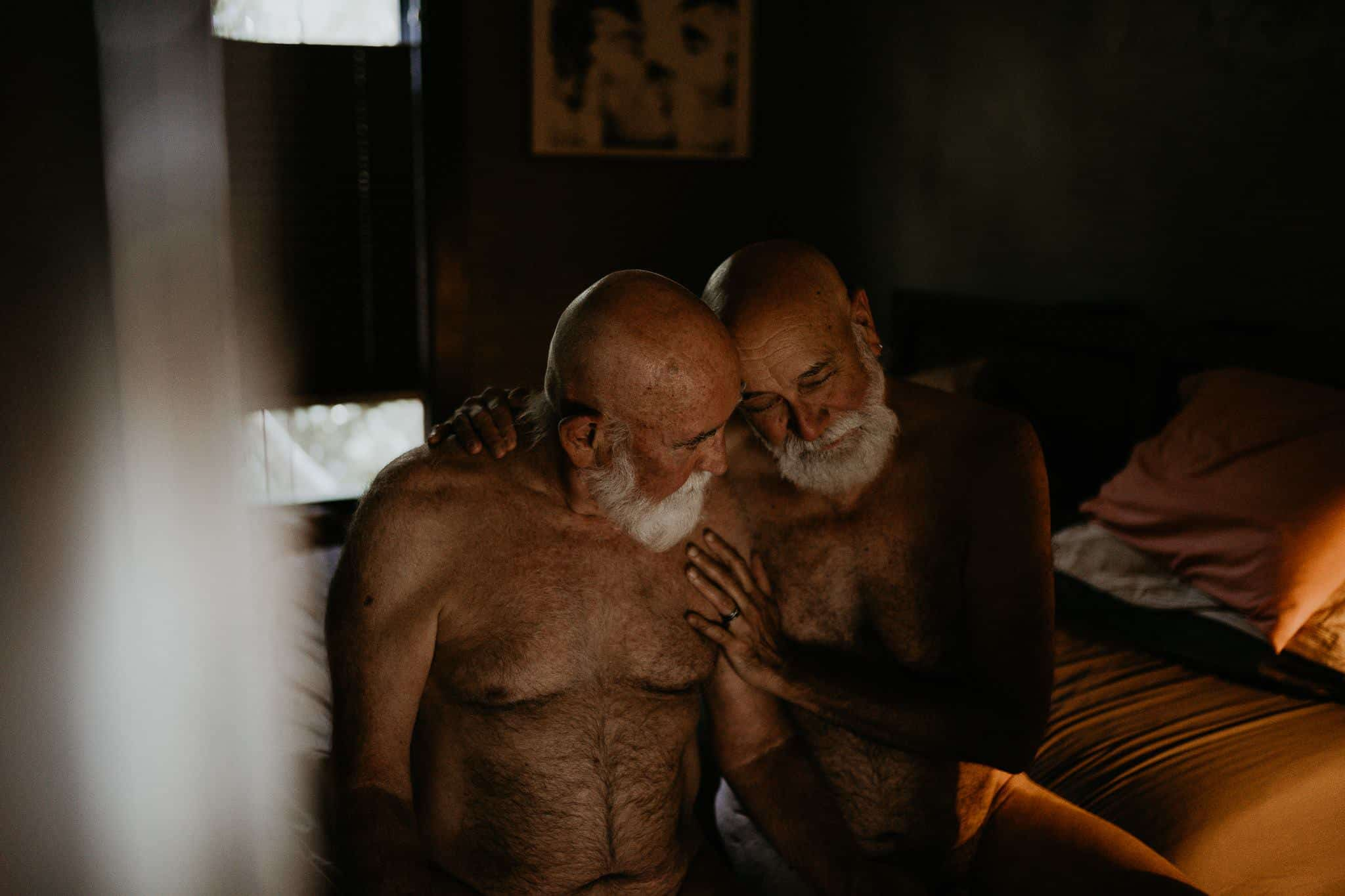 Two elderly gay man embracing each other naked on a bed