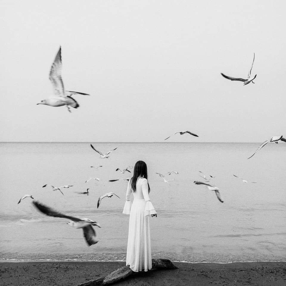 Seagulls surround a woman in a white dress at a beach.