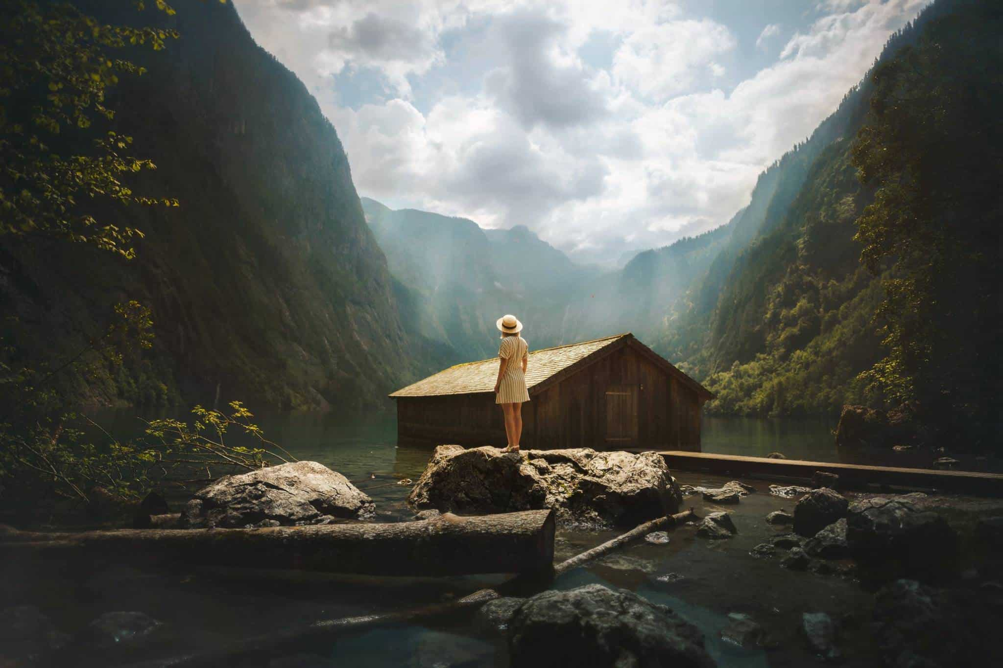 A person is standing on a rock in the middle of a lake and looks at a cabin surrounded by mountains