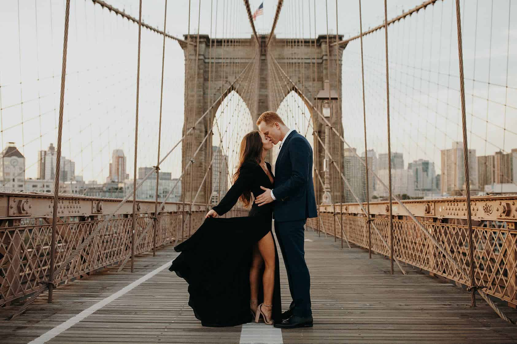 A couple kissing on the Brooklyn Bridge at sunrise