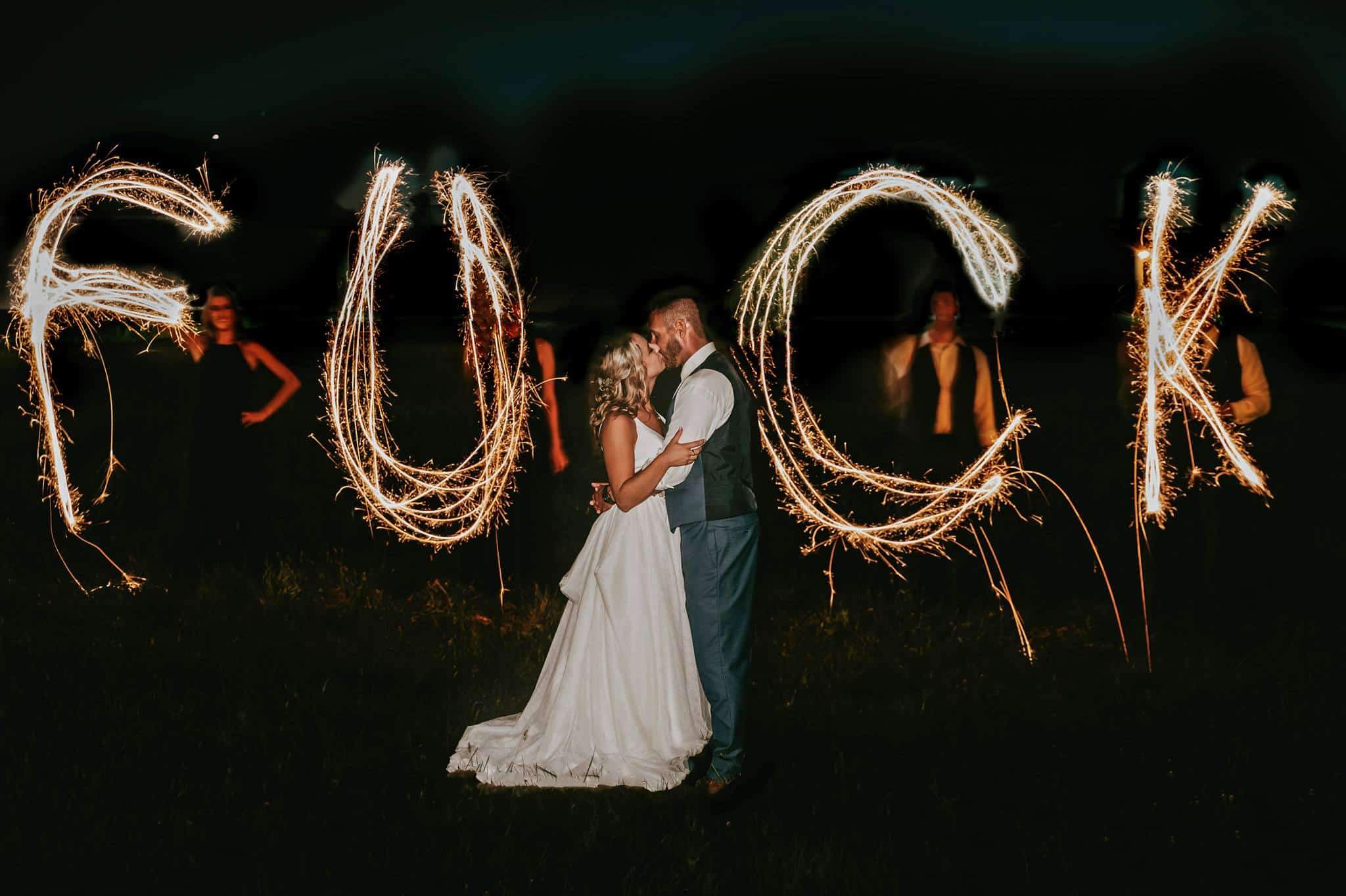 Newlywed are kissing each other while wedding guests wrote the word F-word.