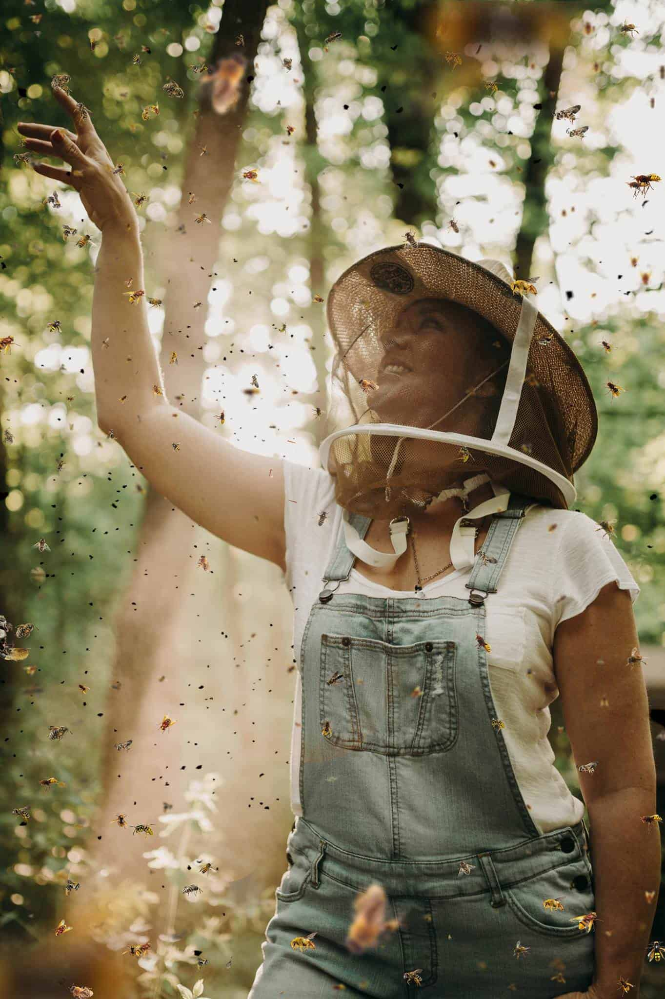 A woman wears a special hat to be protected and tries to touch a bee