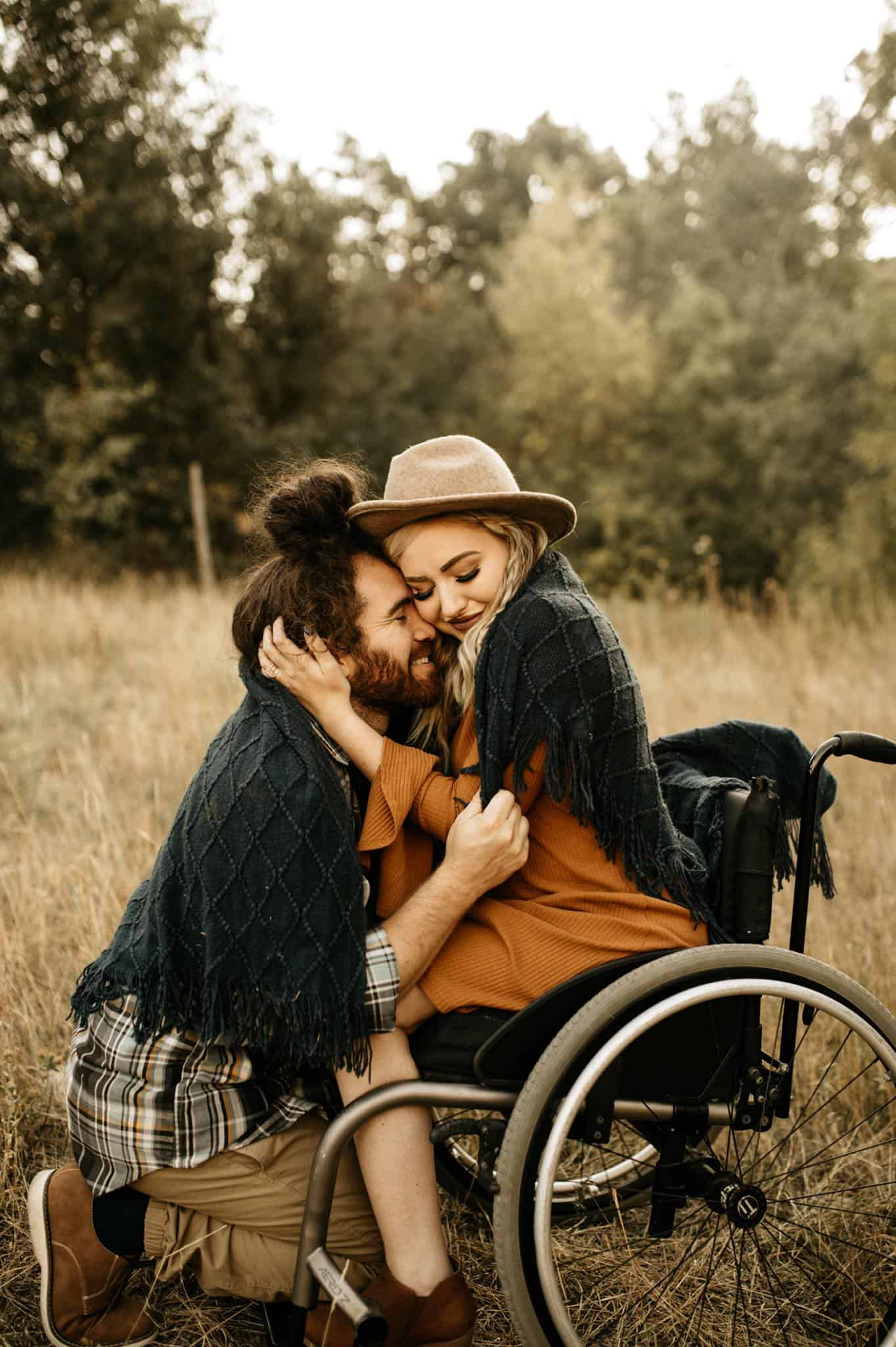 A man kneeing next to his wife who is sitting in a wheelchair embracing him