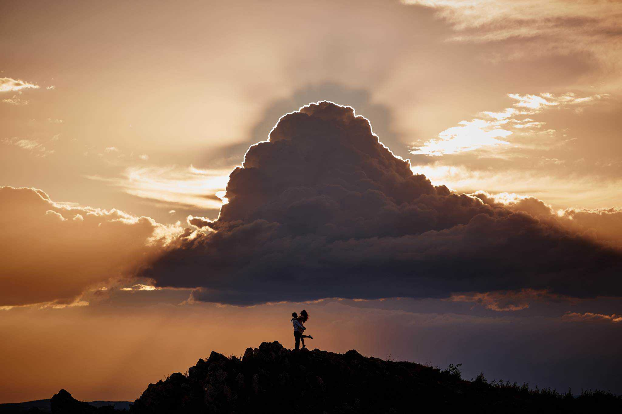 A man picking up his wife in front of a large cloud