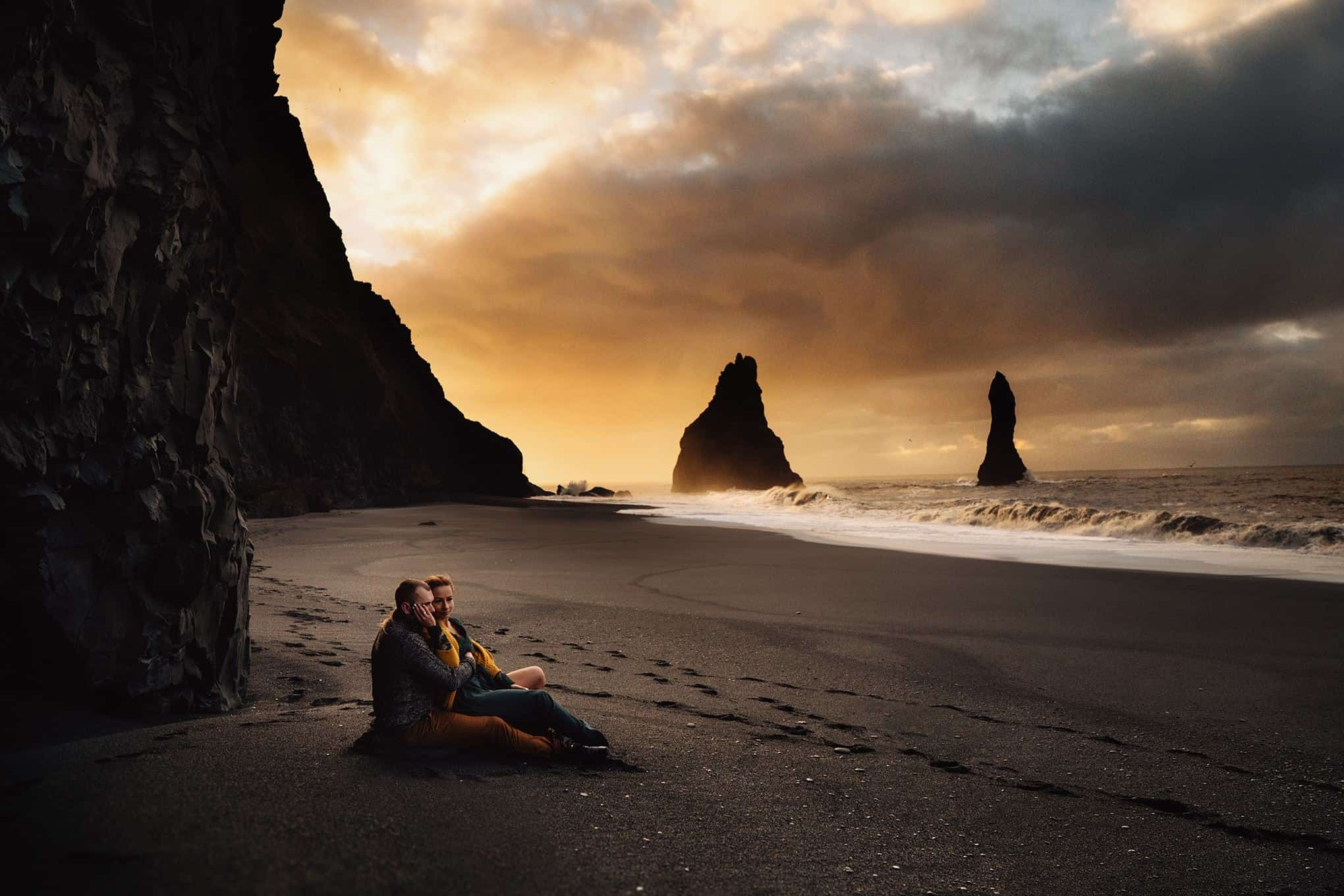 An intimate shot of a couple sitting on the black sand beach at sunrise