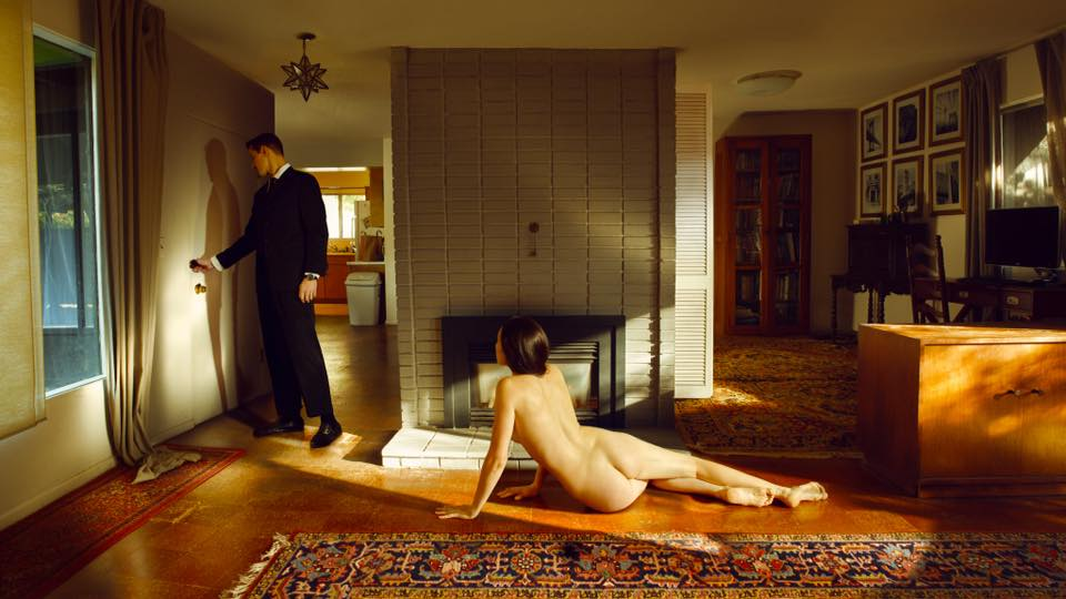 A naked woman is lying on the floor while a man in a suit is leaving the flat