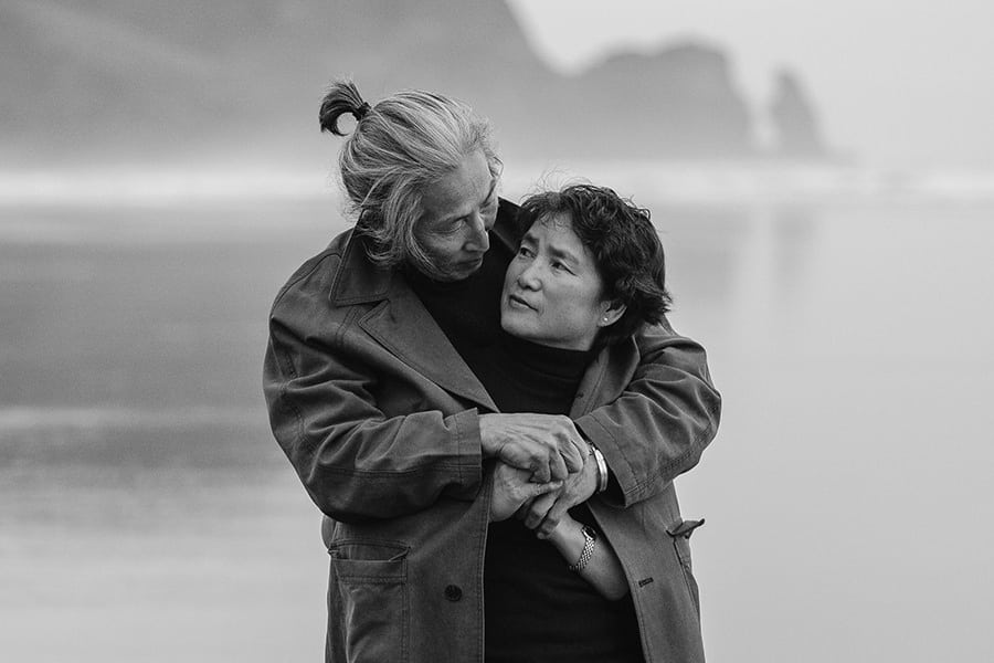 An elderly Japanse man hugging and warming his wife with his jacket on a beach