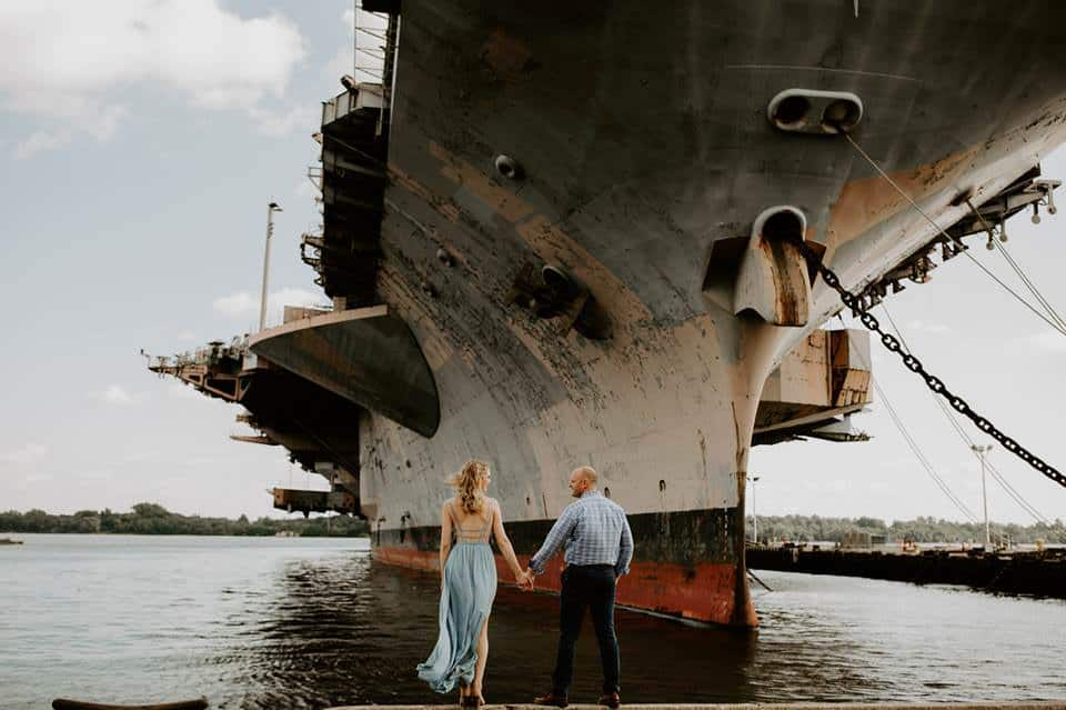 A man and a woman holding hands in front of a large battleship