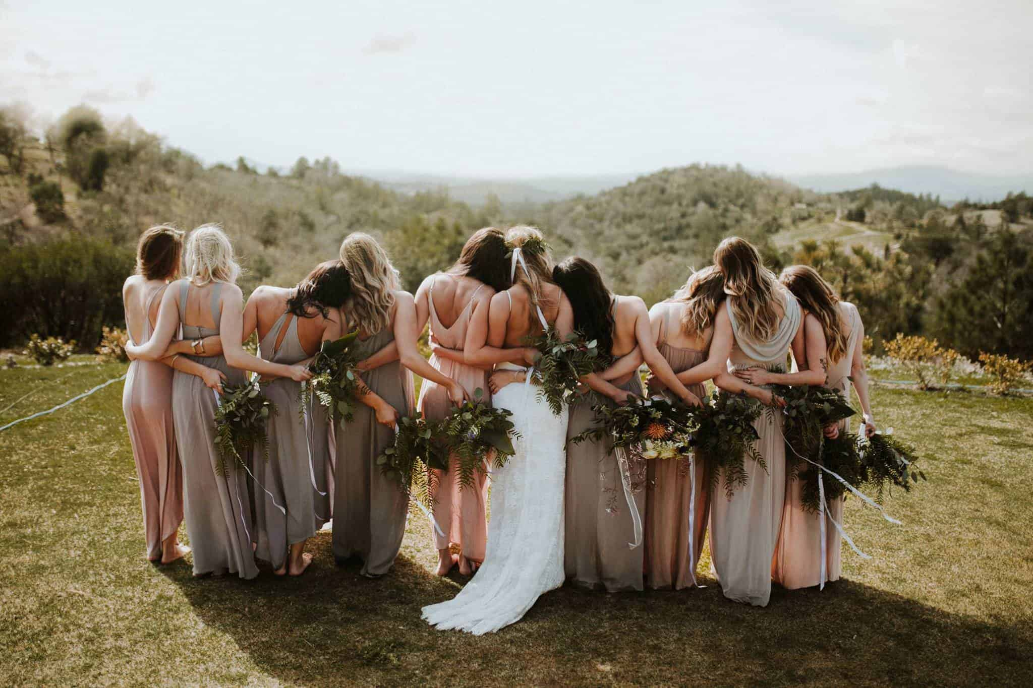 A group of female friends holding each other and bouquets in their hands are showing their backs to the camera.