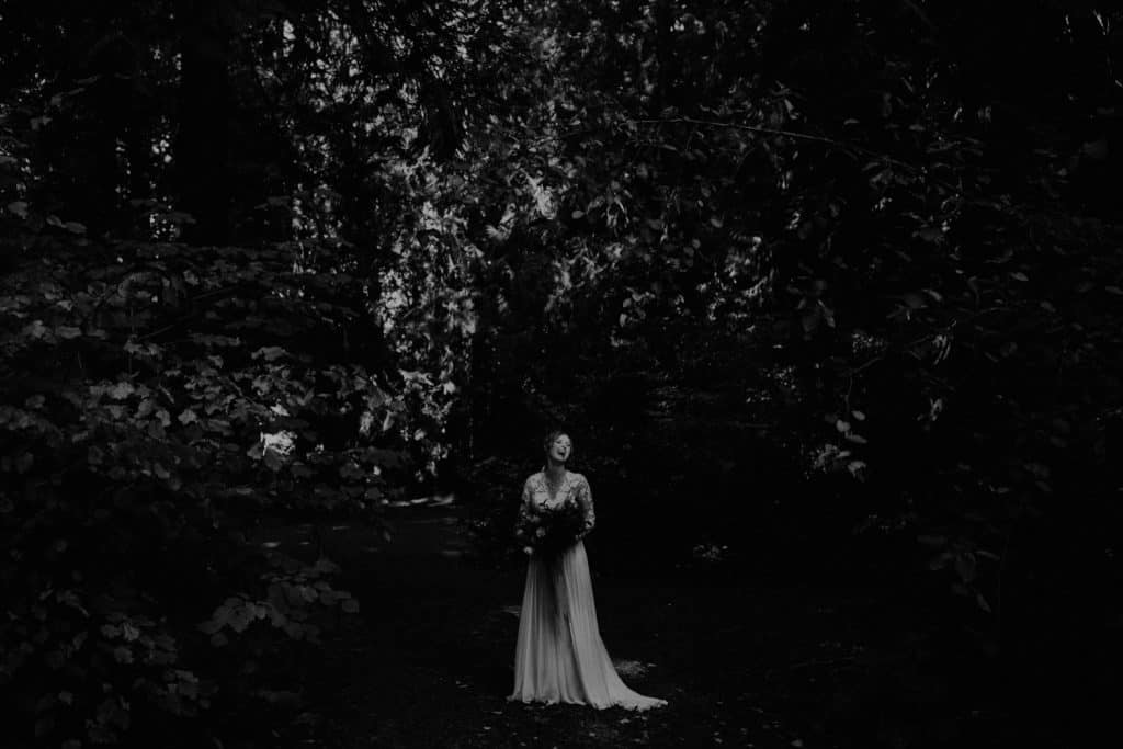 The bride stands between trees in the forest and is smiling