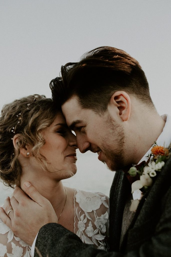Bride and groom are sticking their heads together and are heavily in love