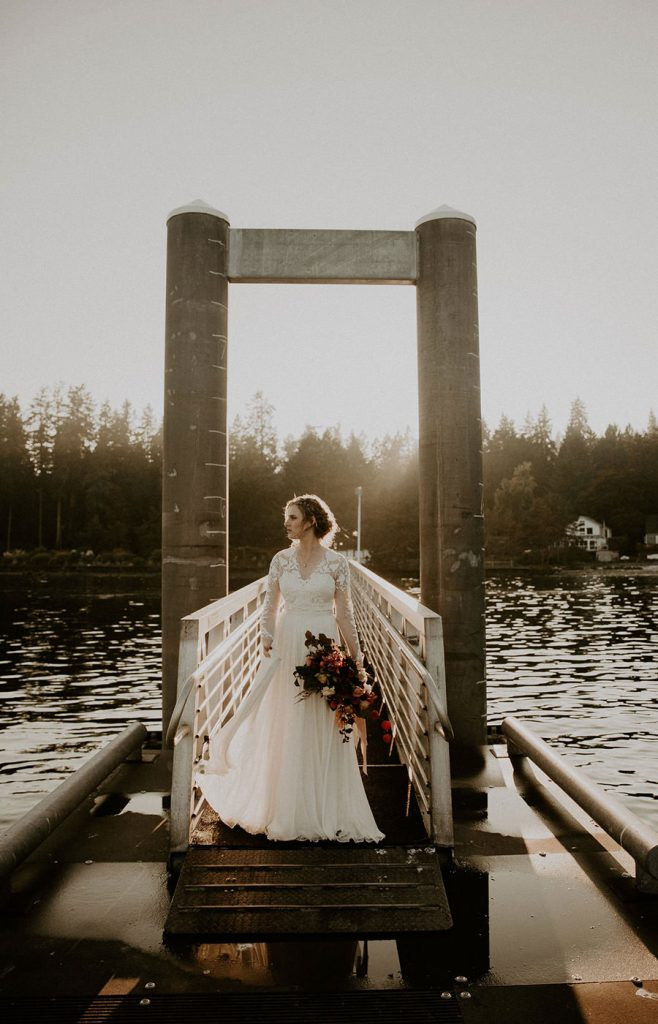 The bride stands on a pier and looks at the ocean
