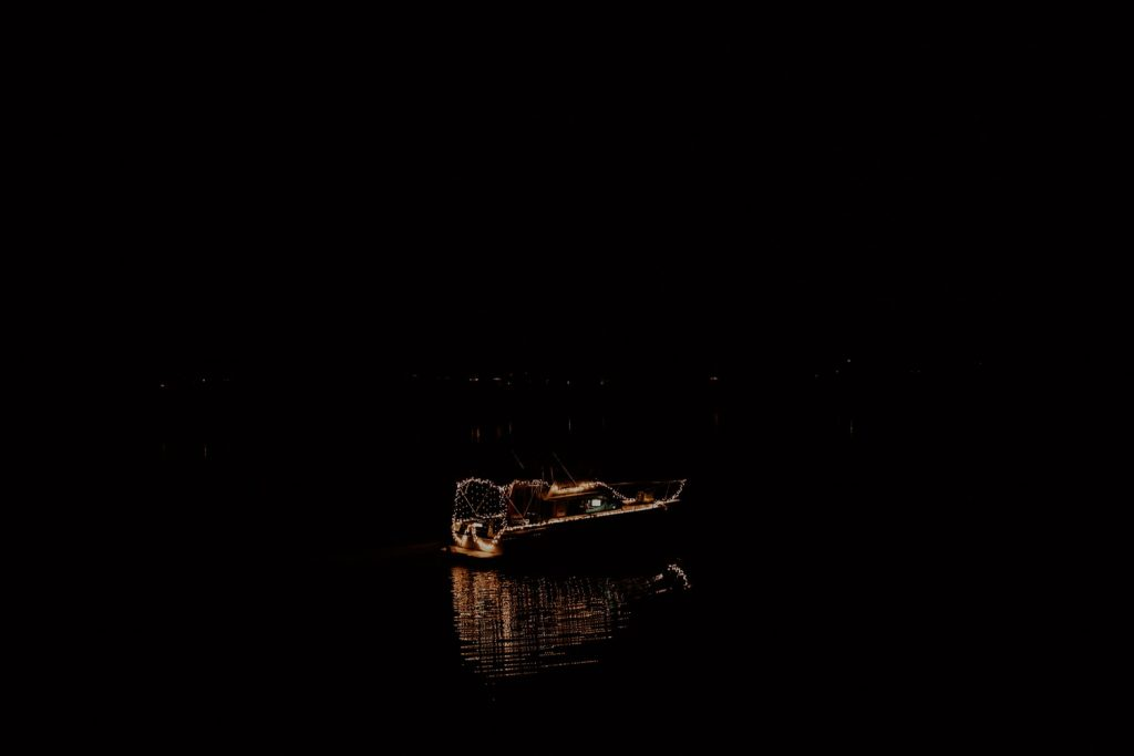 A boat with lights turned on is driving on the dark ocean