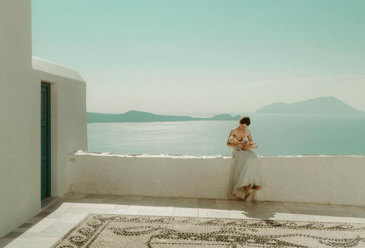 A woman breastfeeding her newborn baby with the ocean in the background