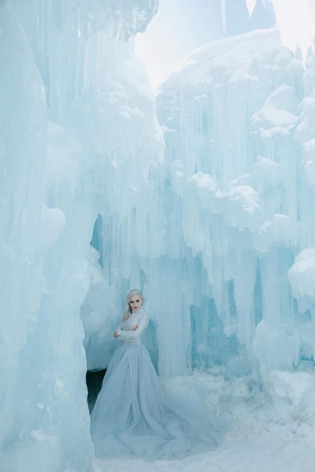 A blonde girl posing in front of frozen rocks.