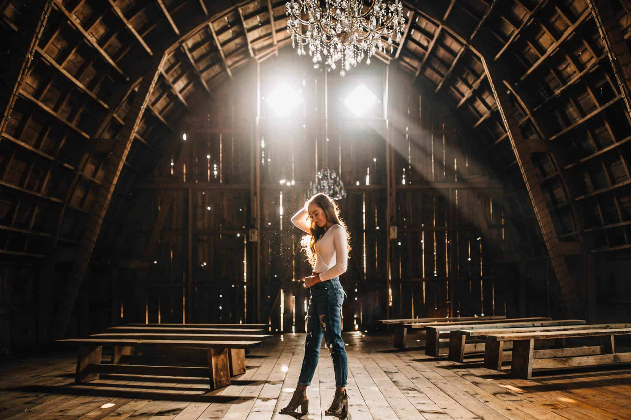 A girl standing in the middle of a barn where the sunlight breaks through the windows