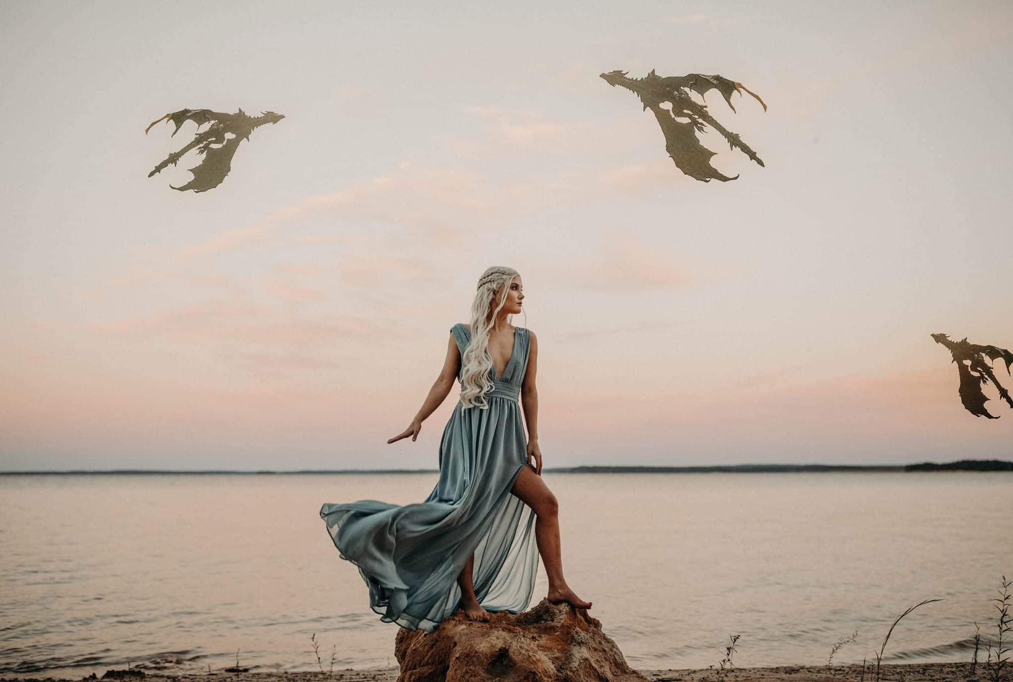 Daenerys Targaryen is standing at a lake and you can see her three dragons flying in the sky