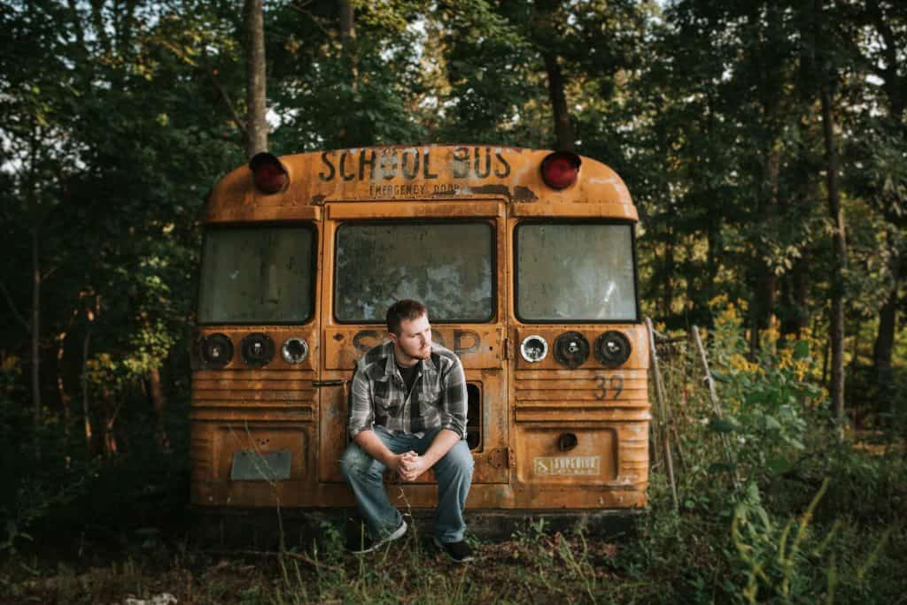 A boy posing in front of an old school bus in the forest