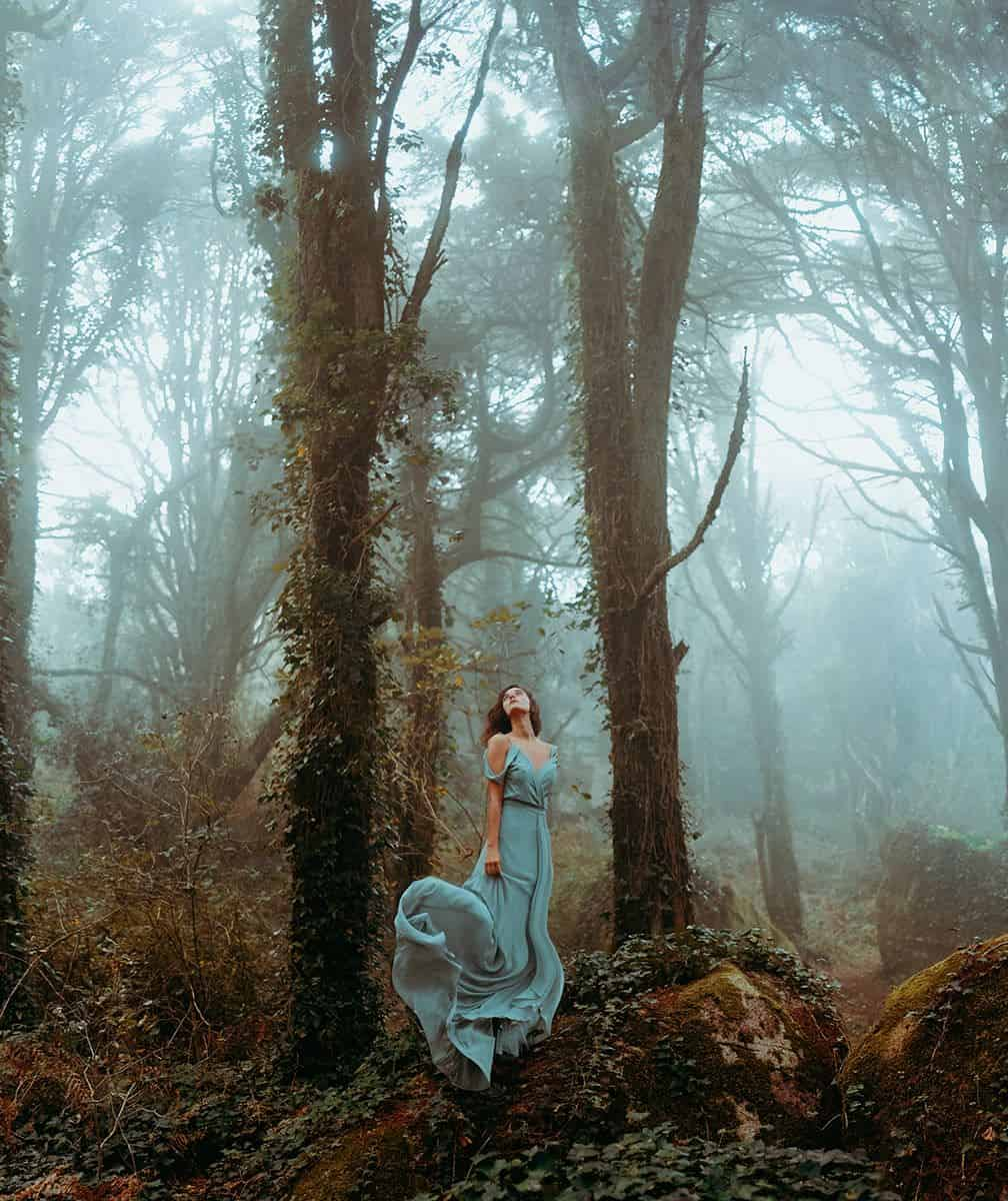 In the middle of a foggy forest a woman with a blue dress stands between two trees
