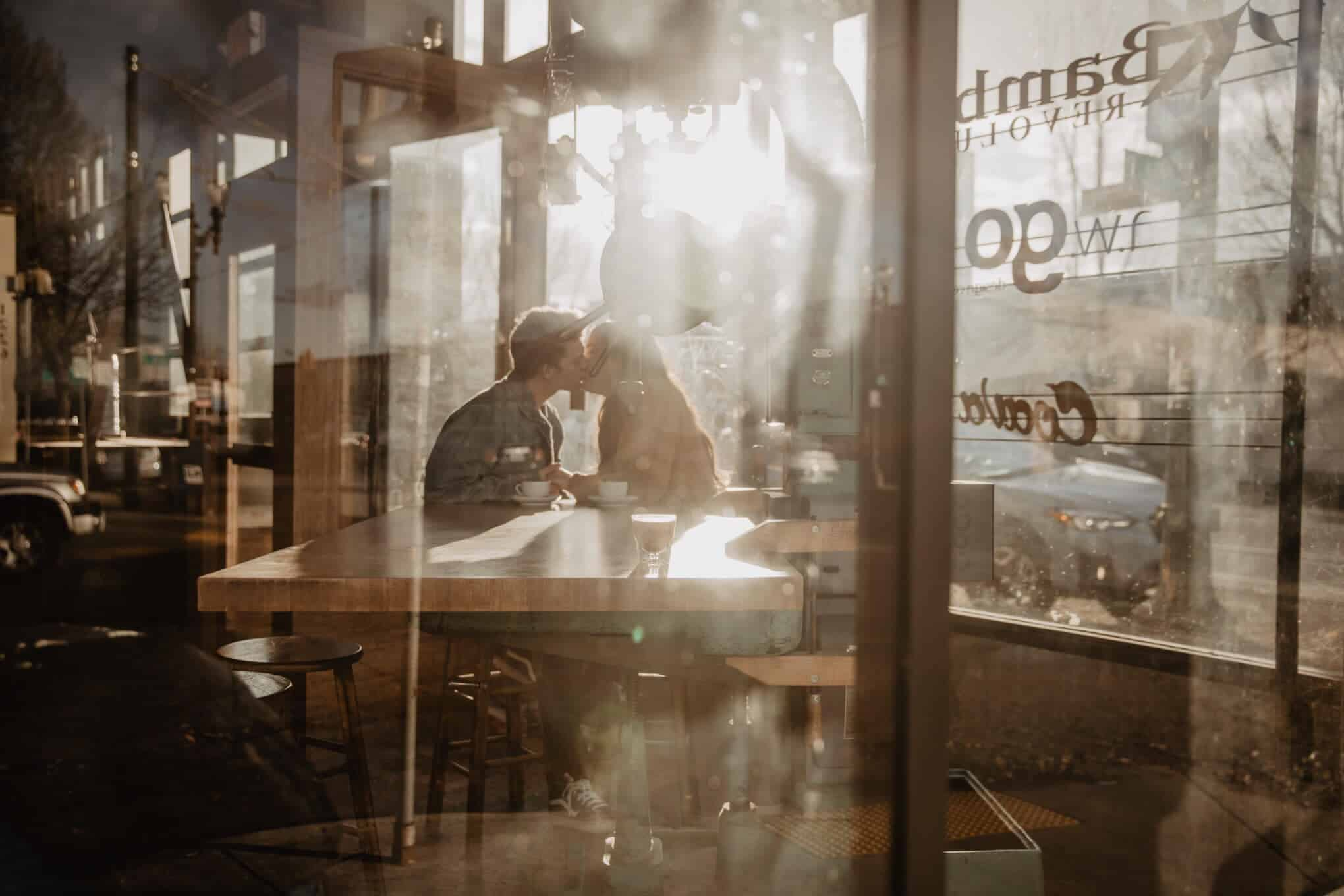 An intimate engagement photo of two lovers kissing in a coffee shop